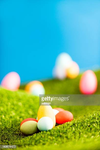Easter sweets on grass hills with blurred background.