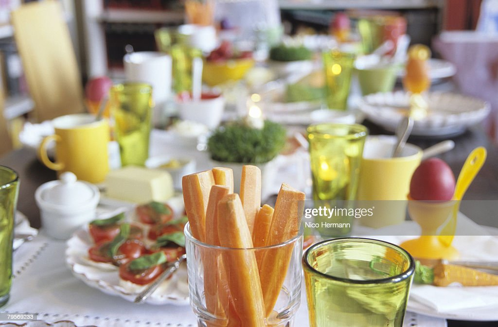 Easter table setting, focus on carrot slices in glass : Stock Photo