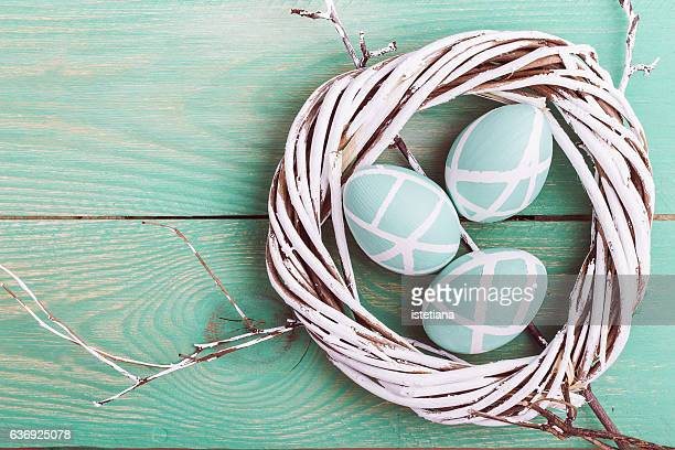 Easter willow tree wreath and pastel Easter eggs on wooden background. Top view with copy space