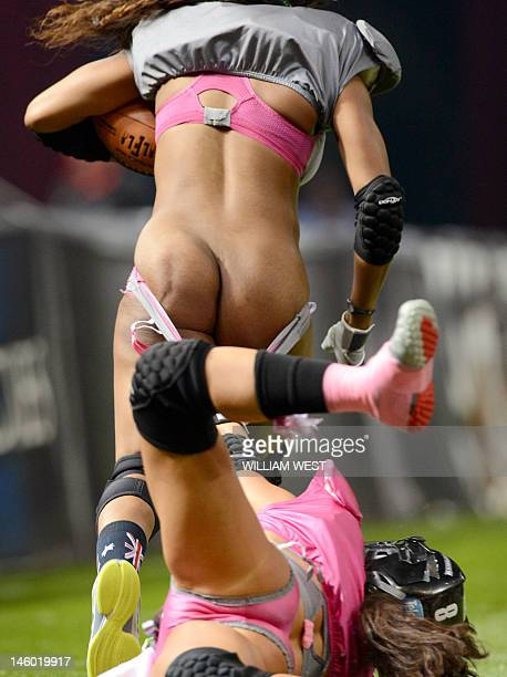Eastern conference player Jaleesa McCray is tackled by Western Conference player Ashley Salerno during their Lingerie Football League AllStars match...