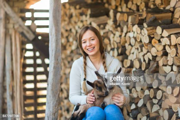 eastern europe: lifestyle-young woman hugging kid goat - cowgirl hairstyles stock photos and pictures