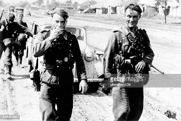 2WW eastern front german soldiers on a village road in Russia One of them playing a harmonika JulyAugust 1943