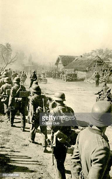 WW2 Eastern Front Line of German soldiers marching through country village Soviet Union Caption reads ' Soviet Union after conquering the place'...
