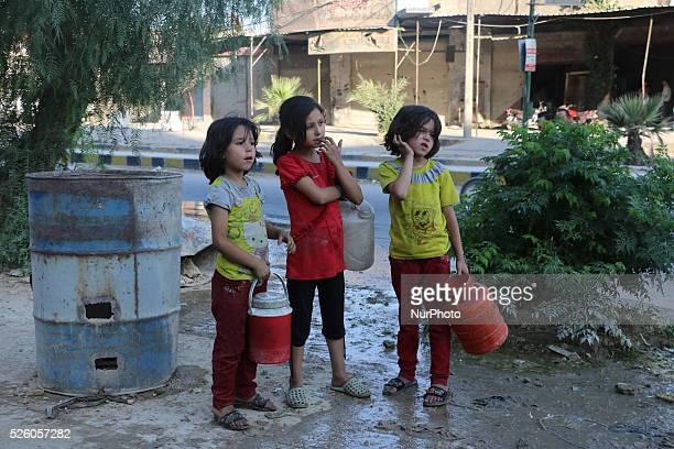 Eastern Ghouta Syria on july 13 2015 Children fill their jerry from the well and waiting for their turn to come due to congestion The suffering of...