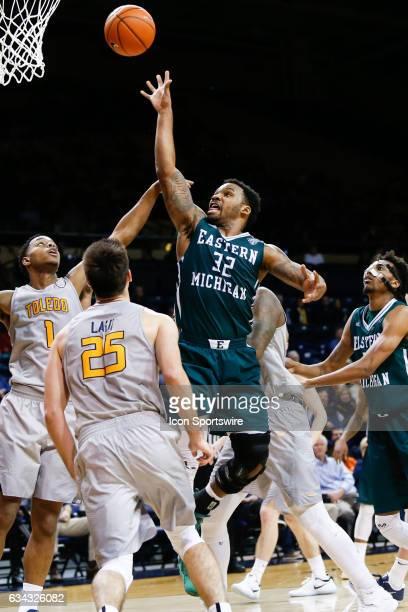 Eastern Michigan Eagles guard Ty Toney shoots over Toledo Rockets guard Jordan Lauf and Toledo Rockets guard Jonathan Williams during a regular...