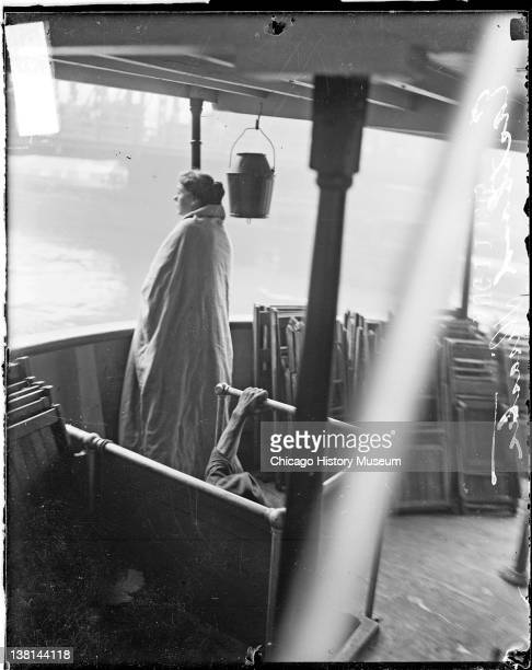 Eastland disaster, female survivor, wrapped in a blanket, standing on upper deck of a boat, Chicago, Illinois, July 24, 1915.