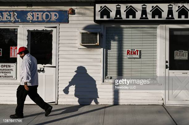 Man wearing a mask walks past an empty store for rent along Main Street in Easport, New York on November 20, 2020.