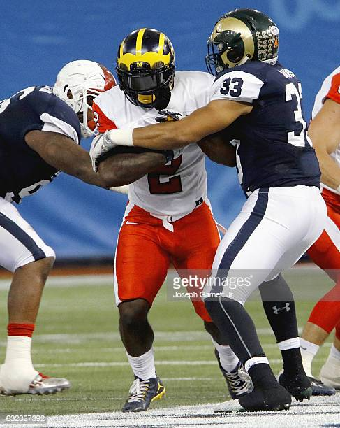 East's De'Veon Smith of Michigan fights his way through the arm tackle West's Kevin Davis of Colorado State during the second quarter of the EastWest...