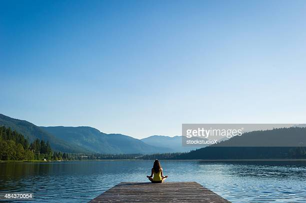 easy pose tranquil lakeside meditation at sunrise - tranquility stock pictures, royalty-free photos & images