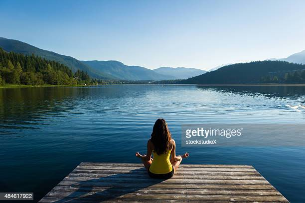 easy pose tranquil lakeside meditation at sunrise - pier stock pictures, royalty-free photos & images