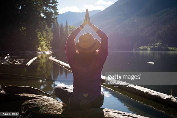 Pose fácil tranquila Lakeside meditação ao nascer do sol