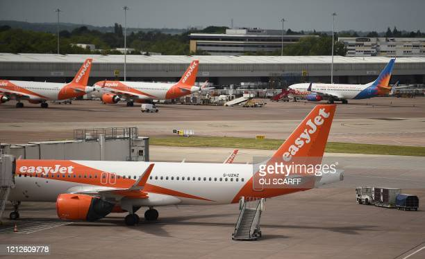 Easyjet aircraft stand on the apron the departure gates at Manchester Airport in Manchester northern England on May 11 where they have begun a trial...