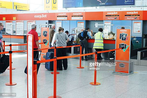 easyjet check-in desks at stansted airport - easyjet stock pictures, royalty-free photos & images