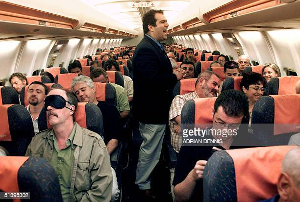 EasyJet tycoon Stelios HajiIoannou laughs as he chats to passengers on the late EasyJet flight from Athens to London 19 September 2000 at Athens...