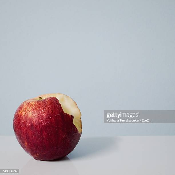 Eaten Apple In Table Against White Background