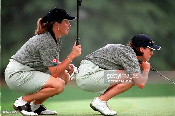 AJ Eathorne contemplates her putt while teammate Lorie Kane keeps her dry as well as collaborates on the shot Canadian Gail Graham digs herself out...
