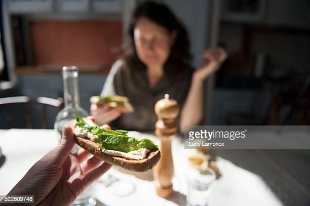 Eating a humus avocado sandwich
