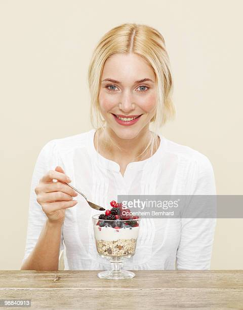 eating a mixture of cereal, berries and yoghurt