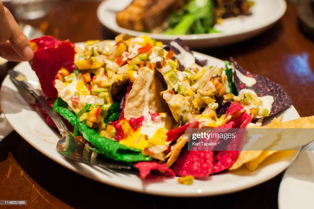 Eating a multi-colored Mexican nachos : Stock Photo
