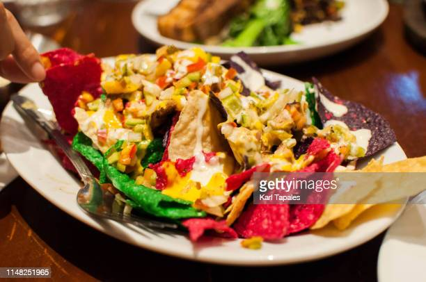 eating a multi-colored mexican nachos - pink taco stock photos and pictures