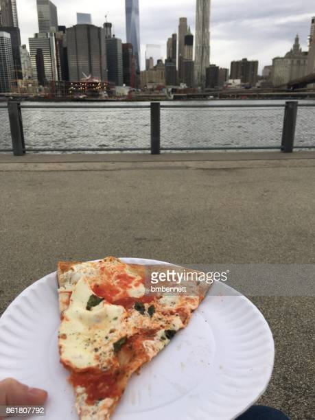eating a slice of pizza in brooklyn with a view of manhattan - paper plate stock photos and pictures