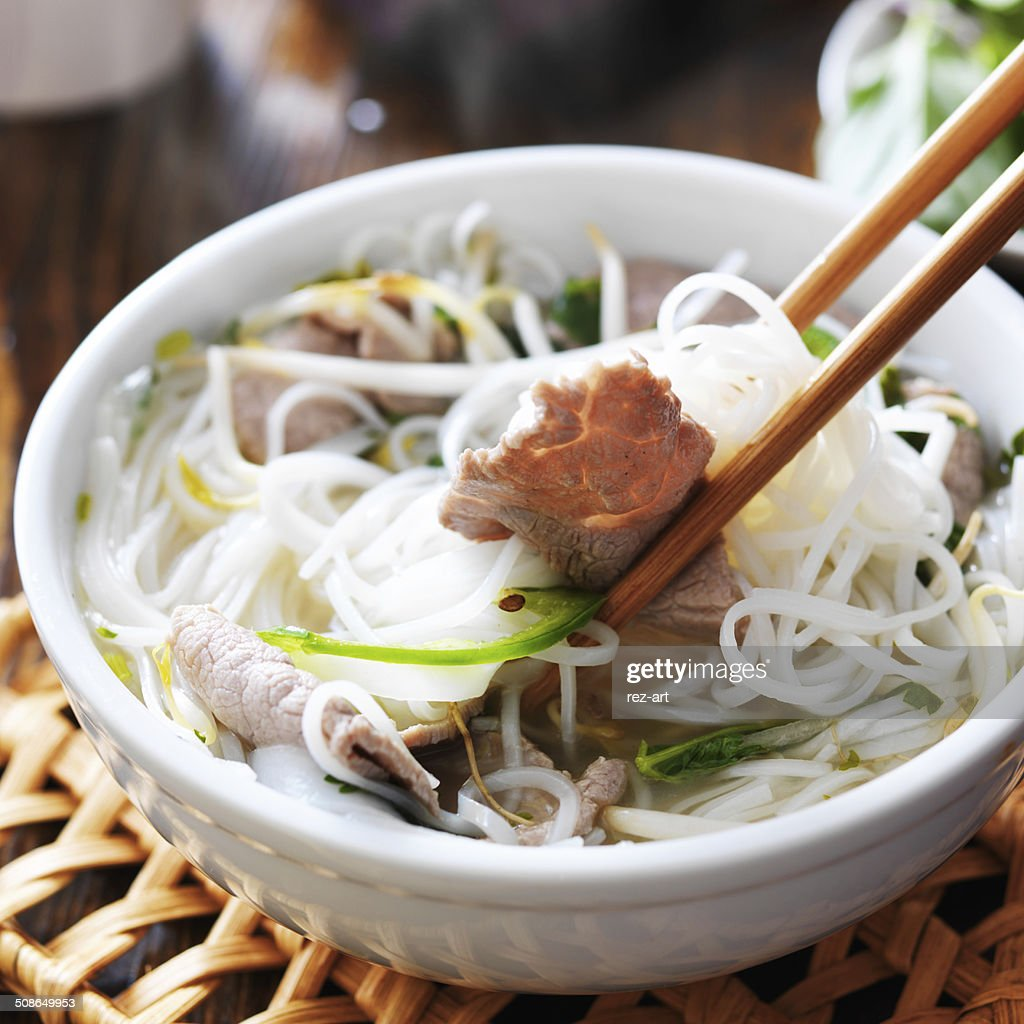 eating a steamy bowl of pho : Stock Photo