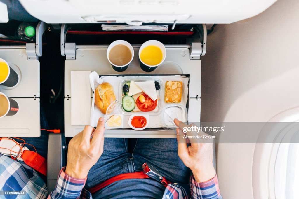 Eating airplane food during a flight, personal perspective directly above view : Stock Photo