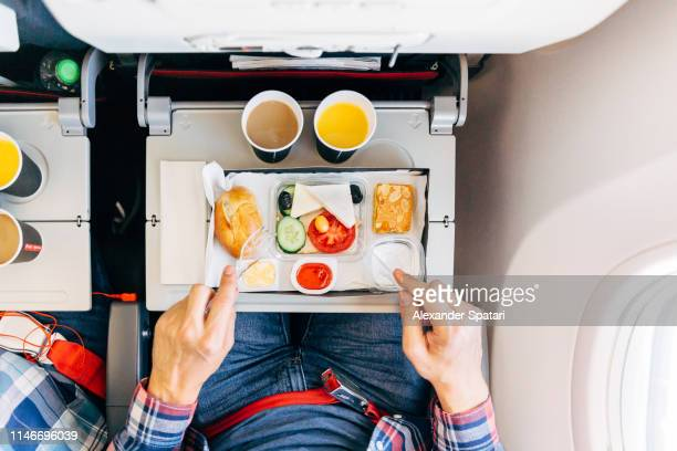 eating airplane food during a flight, personal perspective directly above view - aufwärmen stock-fotos und bilder
