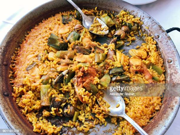 eating authentic paella with rabbit, chicken snails and green beans, valencia, spain - valencia spanje stockfoto's en -beelden