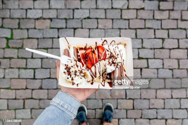 eating belgian waffle with sweet toppings and fresh fruits at the town square, personal perspective view - brussels capital region stock pictures, royalty-free photos & images