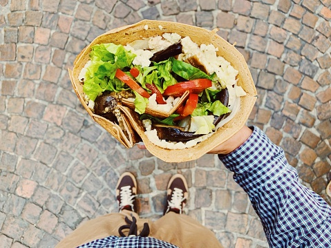 Eating big French crepe pancake with vegetables, salad and cheese, personal persoective view - gettyimageskorea