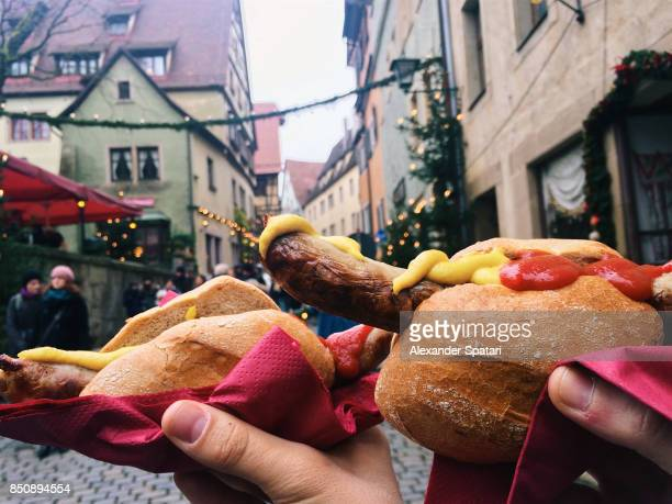 Eating bratwurst at Christmas market, Bavaria, Germany