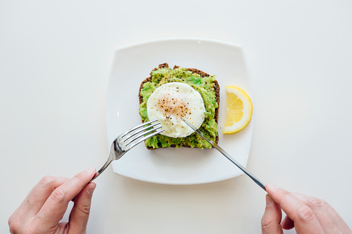 Eating breakfast with avocado toast and egg from personal perspective point of view - gettyimageskorea