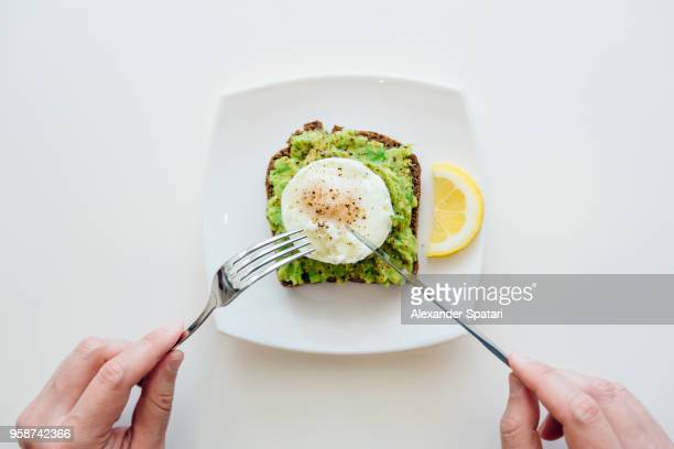 eating breakfast with avocado toast and egg from personal perspective point of view - porzione di cibo foto e immagini stock