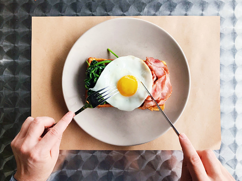 Eating breakfast with Belgian waffle, bacon, spinach and fried egg, personal perspective view - gettyimageskorea