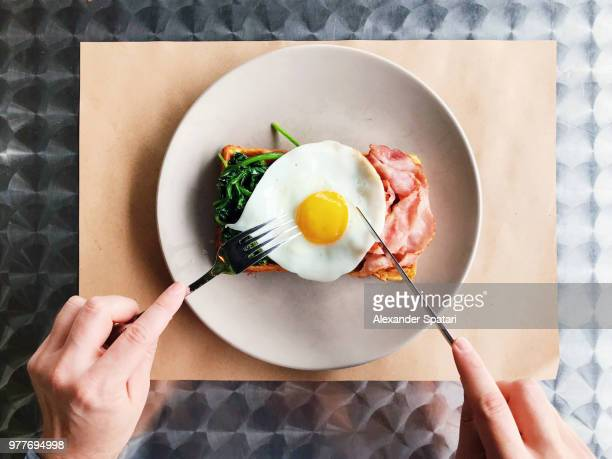 eating breakfast with belgian waffle, bacon, spinach and fried egg, personal perspective view - fried eggs stock pictures, royalty-free photos & images
