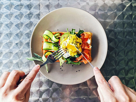 Eating brunch with waffle, avocado, cucumber, salmon and poached egg, personal perspective - gettyimageskorea