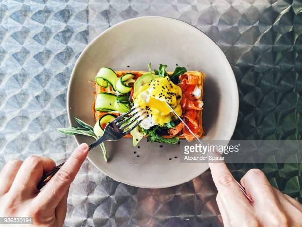eating brunch with waffle, avocado, cucumber, salmon and poached egg, personal perspective - food stockfoto's en -beelden