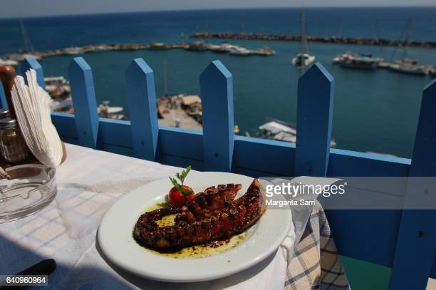 eating by the sea at santorini island. grilled octopus dish, typical of greece - sarri stock pictures, royalty-free photos & images