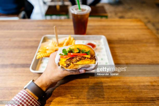eating cheeseburger in a fast food restaurant, personal perspective view - 主観視点 ストックフォトと画像