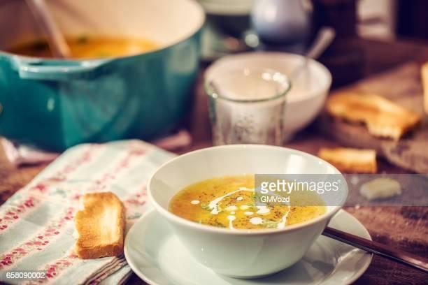 Comer sopa de pollo con zanahorias y chirivías