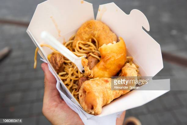 Eating Chinese food from takeaway box on the street, personal perspective