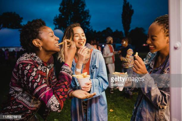 eating chips at a festival - french fries stock pictures, royalty-free photos & images