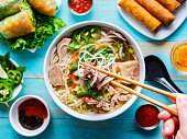eating colorful vietnamese pho bo with chopsticks