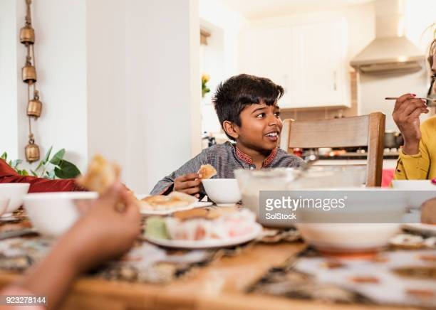 eating dinner with his family - eid mubarak stock pictures, royalty-free photos & images