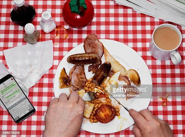 Eating English Breakfast, tea and mobile on table