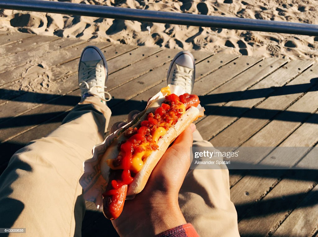 Eating famous New York hot dog at Coney Island Boardwalk, personal perspective : Stock Photo