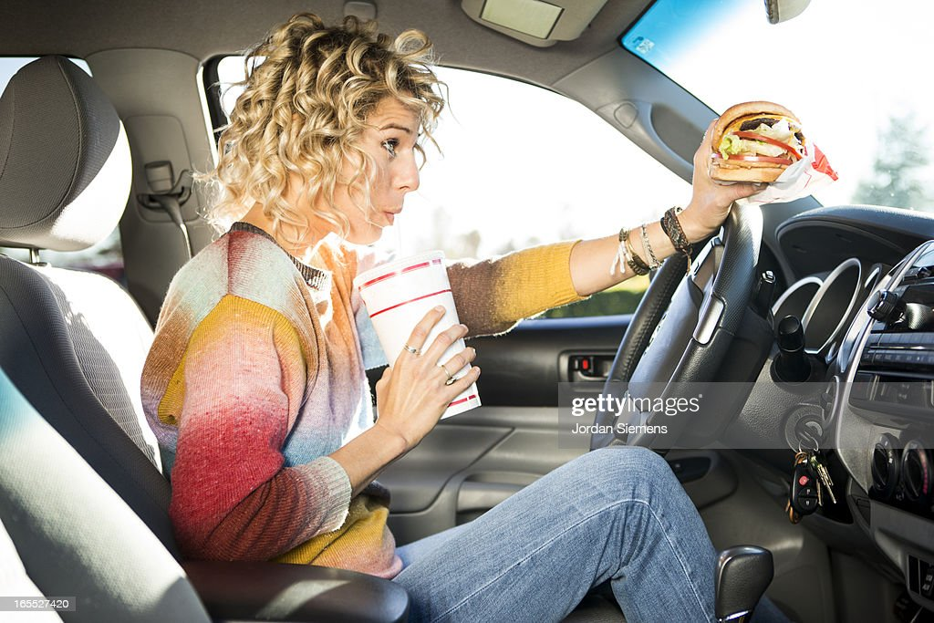 Eating fast food hamburgers and driving. : Stockfoto