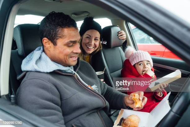 eating fast food in the car - indulgence stock pictures, royalty-free photos & images