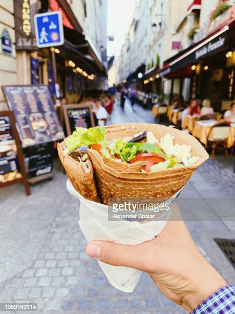 eating french crepe pancake with cheese and fresh vegetables on the street, personal perspective - pancakes stock pictures, royalty-free photos & images